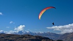 Tandem paraglider in the sky above Queenstown Hill