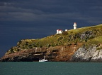 Taiaroa Head with lighthouse, small boat, and dark clouds