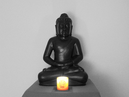Buddha sitting with candle