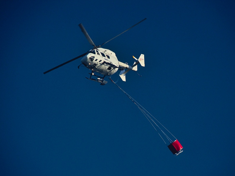 Helicopter flying with fire bucket