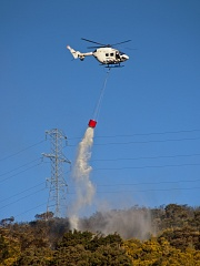 Helicopter putting up fire near power lines