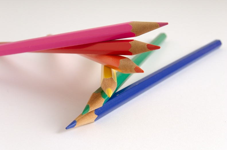 Six bright colour pencils stacked on top of each other