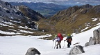 Trampers traversing snow above tarns