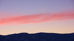 Ribbon of pink cloud above snowy mountains