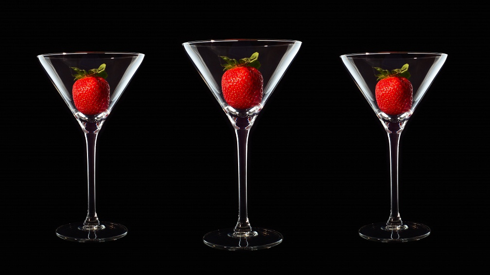Three Martini cocktail glasses with red strawberries