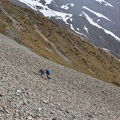 Two trampers climbing up scree slope