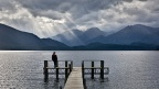 Man on Marakura Yacht Club jetty and dramatic clouds