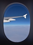 Airplane window with a wing and clouds