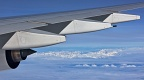 Airplane wing with jet engine and Southern Alps