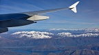 Airplane wing, mountains, and a lake