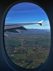 Airplane window with a wing and Canterbury Plains