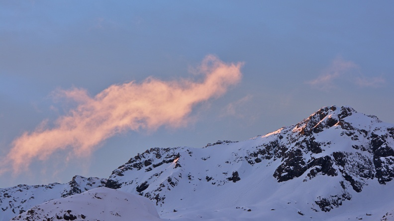 Pinky cloud and first sunrays on a mountain top