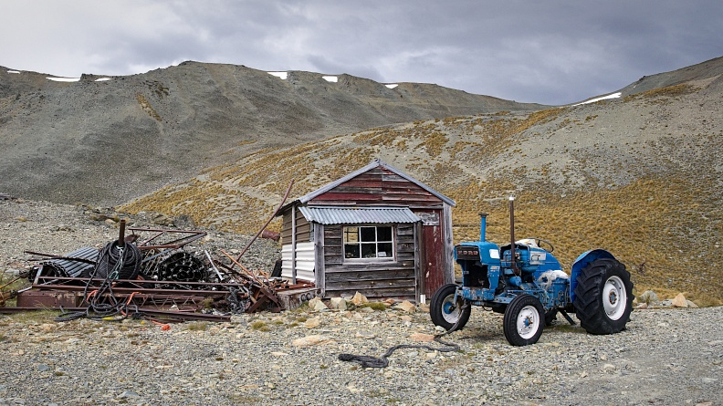 Old tractor, hut, and pile of stuff