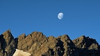 Moon above sunlit rocky ridge