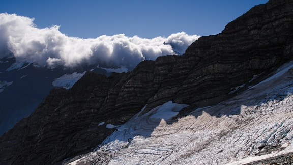 Layered rock, snow, and clouds