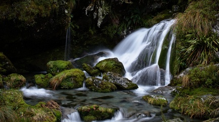 Small waterfall with green mossy boulders